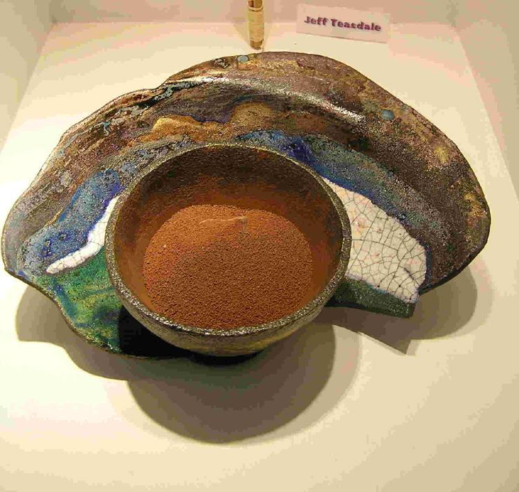 Shutlingsloe Vessel�; raku ceramic, glazes and acrylic, sand and stone (at The Art walk, Manchester Airport). Two-part piece, the shallow �saucer� depicts in glazes and acrylic, a �diorama� of part of the landscape around Shutlingsloe, a peak above Macclesfield Forest, and visible from all parts of Cheshire & beyond.